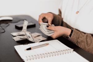 Mulher contando cédulas de dinheiro para simbolizar o tema Simulador do Tesouro Direto