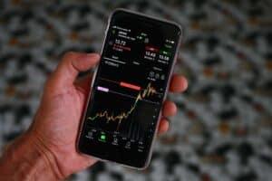 foto de celular com gráficos, representando ações da apple e tesla