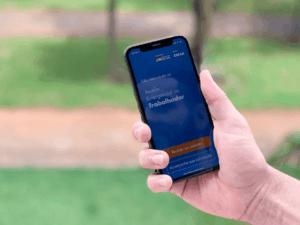 Imagem de uma pessoa acessando seu celular para alterar a senha do Caixa Tem