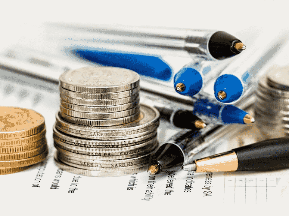 moedas e canetas, representando bancos tradicionais aumentam tarifas bancárias
