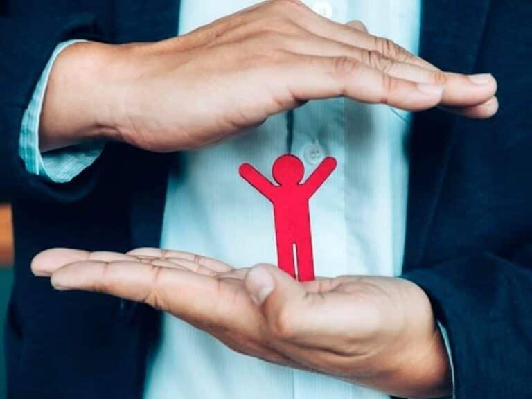 as mãos de uma pessoa envolvem um boneco que representa o seguro de vida e contra acidentes pessoais