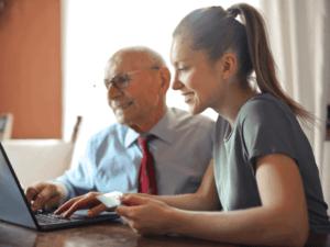 mulher e idoso utilizando computador, representando cartão bndes para mei