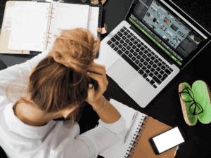 mulher preocupada no computador, representando desemprego em julho