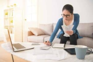 mixed race asian chinese housewife calculating accounting new year budget holding a receipt using calculator sitting on sofa in the living room at home