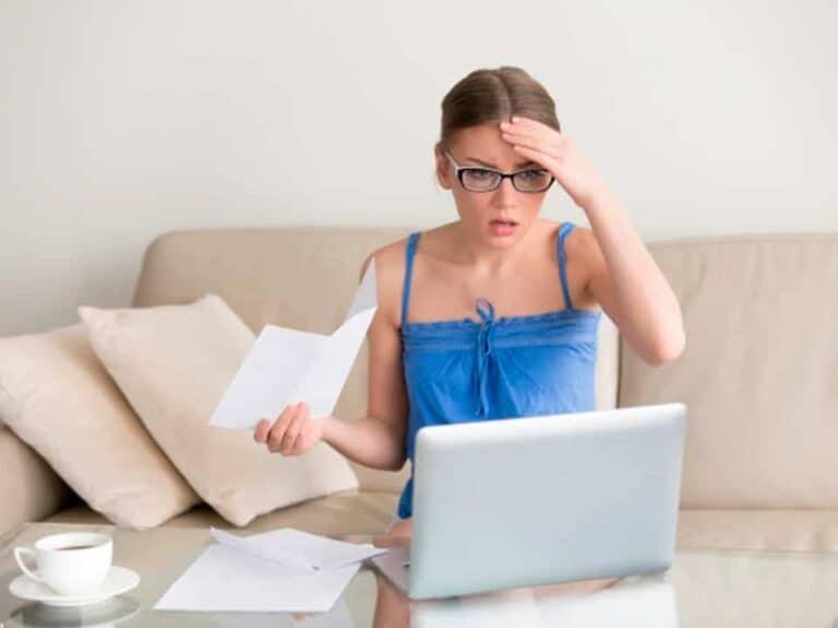 mulher sentada em frente ao computador com vários papéis em sua mão e cara de preocupada por estar endividada
