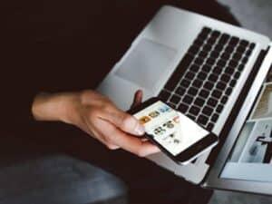 Imagem de uma pessoa usando o celular e computador para ver as novidades sobre a notícia em que o Guiabolso lança transferências instantâneas