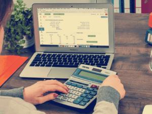 pessoa no computador com calculadora, representando mobills pagará contas