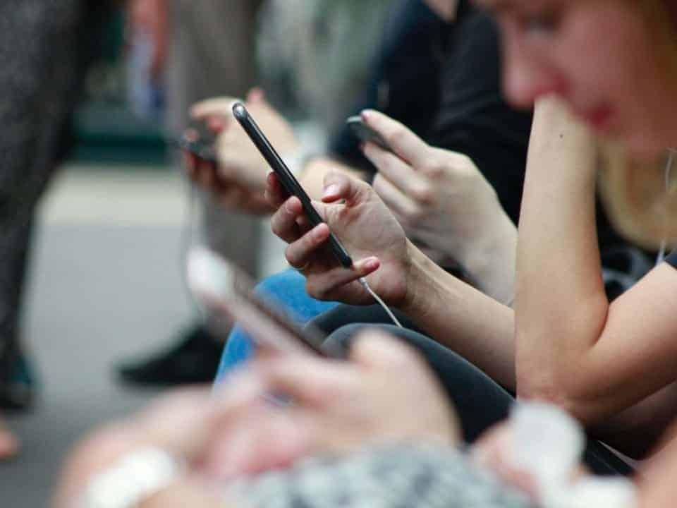 """Imagem de uma série de pessoas usando o celular como forma de representar a notícia """"modelos similares ao PIX no mundo"""""""