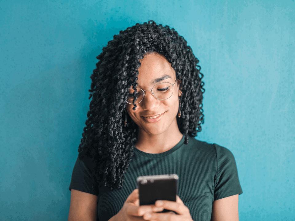 Imagem de uma jovem usando o celular para acessar os novos CDBs do PagSeguro