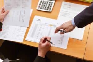 Imagem que representa o conteúdo sobre prescrição de dívidas, você pode ver uma mesa com vários papéis e calculadoras