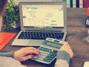Mulher usando notebook e calculadora para fazer o seu planejamento financeiro pessoal