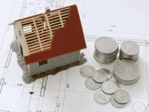 casa em miniatura e moedas, representando portabilidade de financiamentos imobiliários