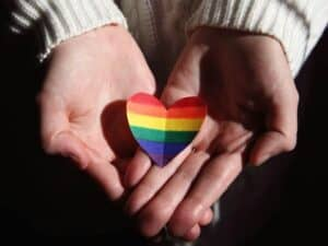 Imagem de uma pessoa segurando um coração de papel com as cores do movimento LGBTI+, representando o lançamento do Pride Bank