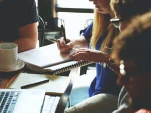 Imagem de jovens conversando em uma mesa, representando o programa de estágio Neon 2020