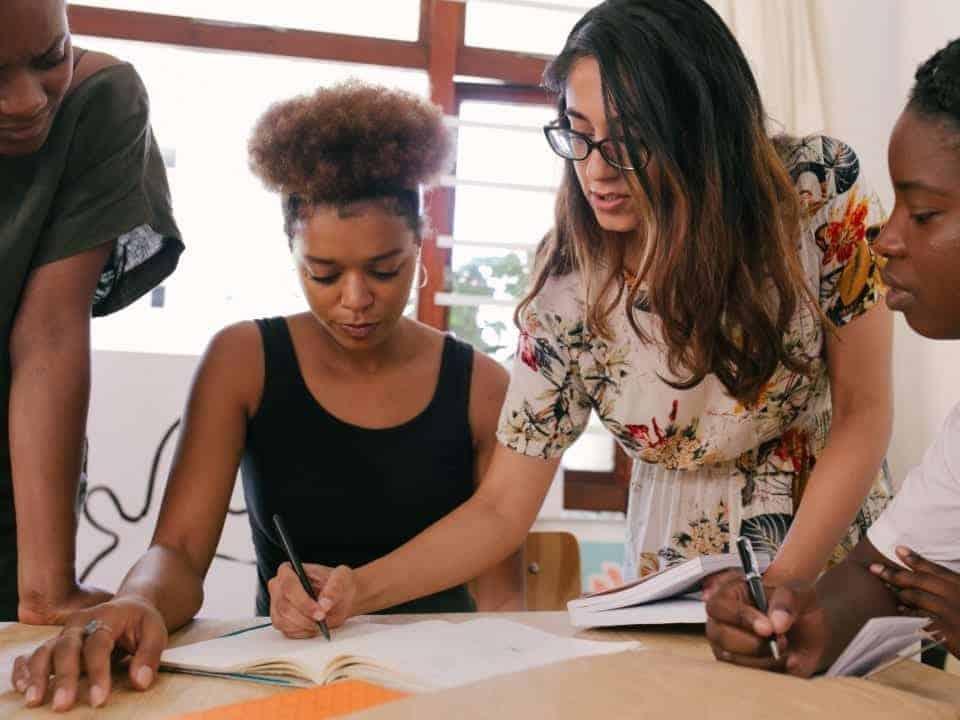 Imagem de jovens em uma mesa trabalhando em um projeto, imagem representa a abertura do programa de trainee do Itaú