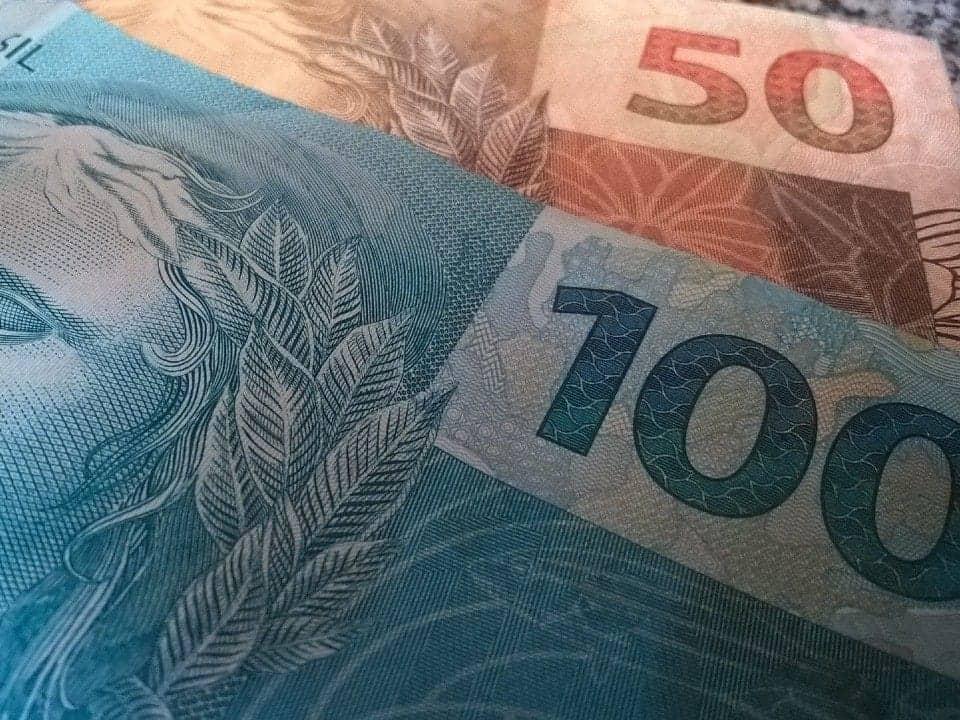 Imagem de uma nota de R$100 e uma de R$50, representando a queda na economia em 2020