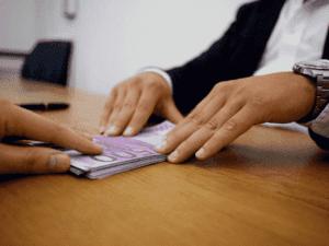 pessoa recebendo dinheiro, representando reclamações sobre crédito consignado