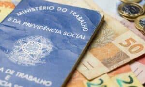 Notas de dinheiro acompanhado de moedas, carteira de trabalho, lupa, calculadora encima da mesa