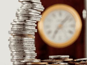 pilha de moedas e relógio, representando tesouro direto dá calote?
