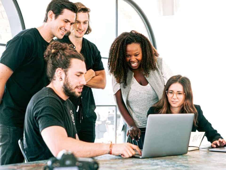 Imagem de estudantes em um ambiente de trabalho, simbolizando as vagas de estágio e trainee que estão abertas em todo o Brasil