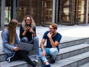 Imagem de estudantes recém-formados conversando, grupo é contemplado pelas vagas na Ambev em seu processo de trainees