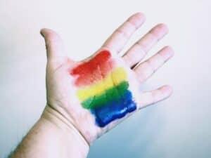Imagem de uma mão aberta com a pintura da bandeira LGBTQ+ representando a abertura de vagas para o público trans em SP