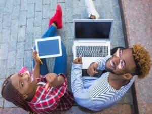 Jovens negros sentados na calçado acessando tablet e notebook representando trainee na Bayer