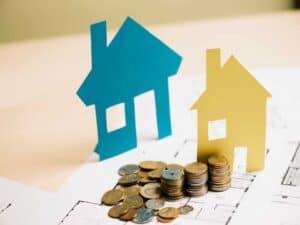 pilhas de moeda e casas de papel representando fundos imobiliários ou imóveis