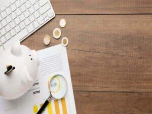 Mesa com cofrinho, lupa, papéis , moedas e teclado, representando o conteúdo que fala sobre o é carta de crédito de um consórcio