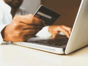 homem no computador com cartão, representando compras internacionais com cartão pré pago