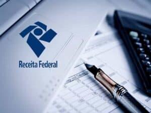 Logo da Receita Federal em notebook, caneta, papel e calculadora representando contribuintes na malha fina