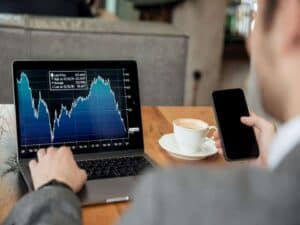 homem em frente ao notebook consultando ações representando empresas cancelam IPOs