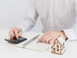 mesa com maquete de casa, mão em calculadora e mão em caderno, simbolizando o empréstimo com garantia de imóvel Caixa