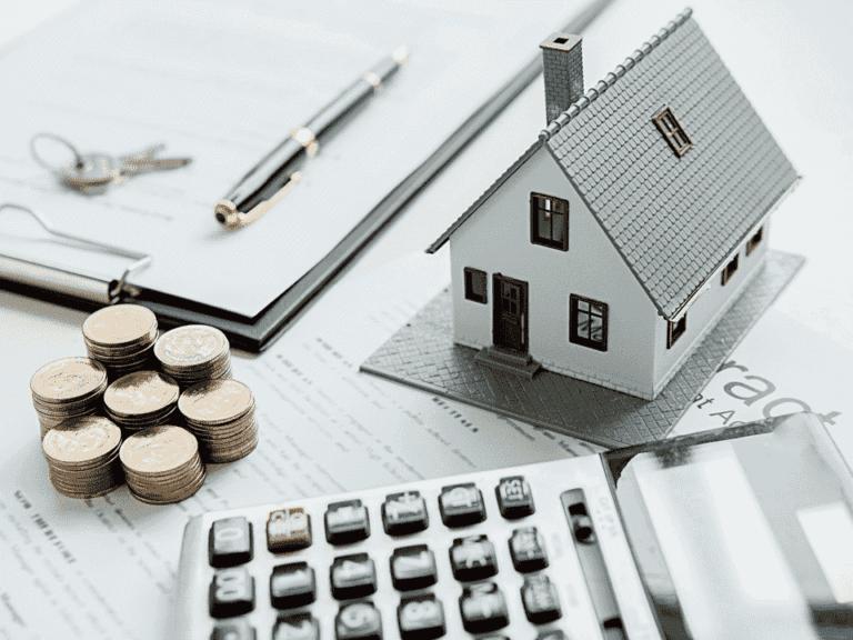 casa em miniatura, moedas e calculadora, representando inflação nos contratos de aluguel
