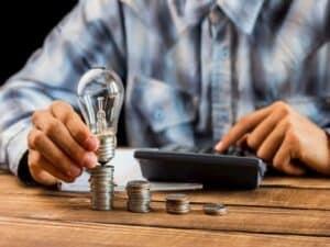 homem usando calculadora e pilhas de moedas epresentando nova CPMF