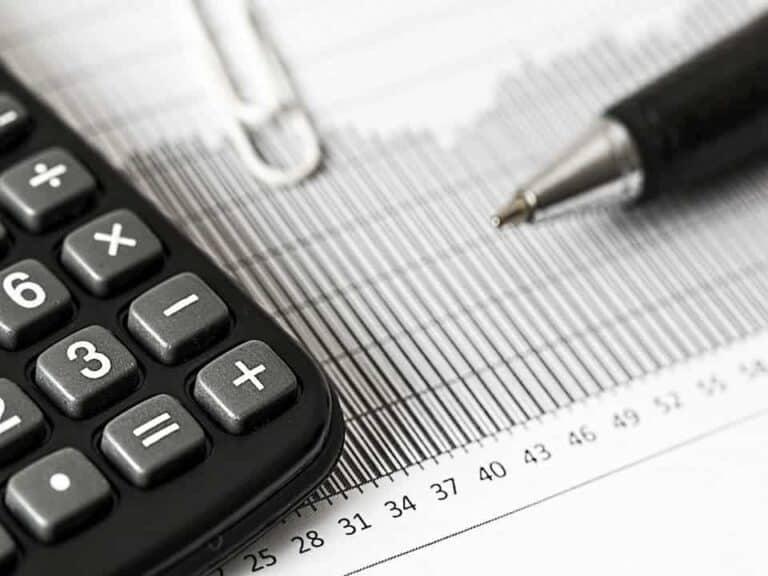 calculadora, papel, caneta e cliprepresentando queda do Tesouro Selic