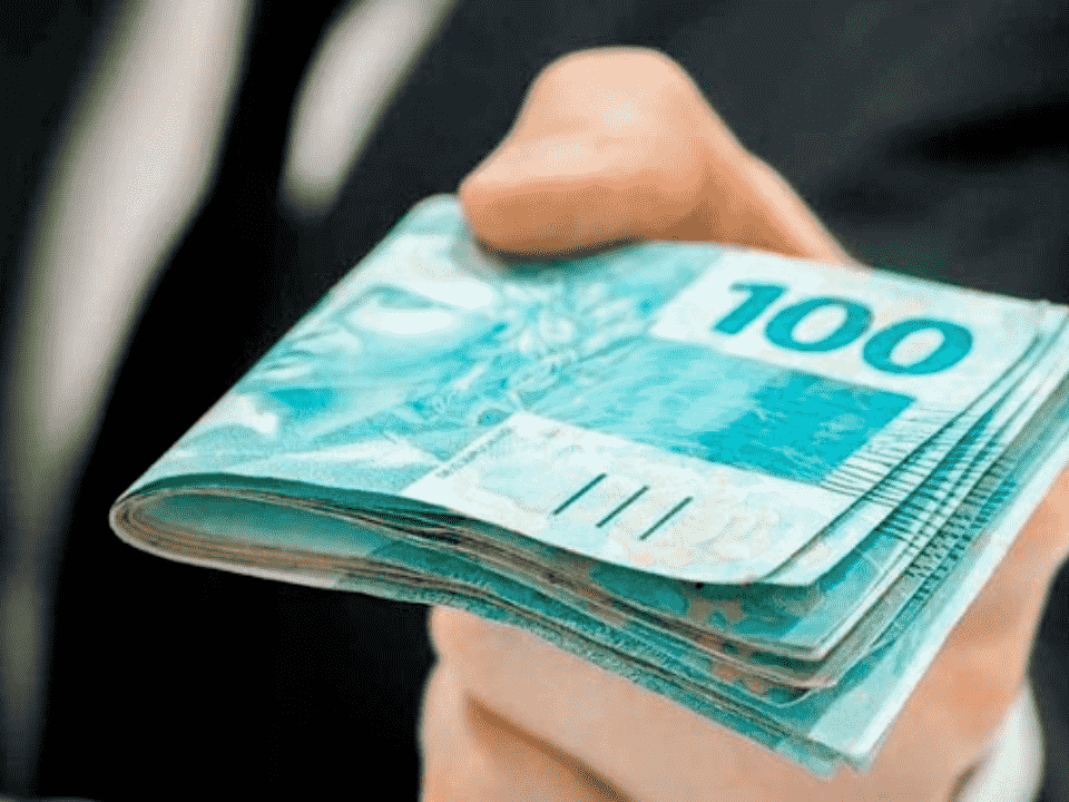 homem entregando cédulas de R$ 100, representando R$ 50 milhões do Pronampe