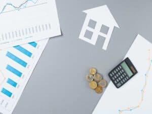 Visão aérea do balcão de negócios com moedas empilhadas, calculadora, recorte de casa e gráfico representando reajuste de contrato de aluguel