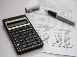 Calculadora, papel e caneta representando Rentabilidade de CDBs, LCIs e LCAs