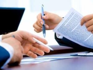 close em mãos de pessoas em cima de uma mesa com papéis e notebook representando segunda fase da reforma tributária