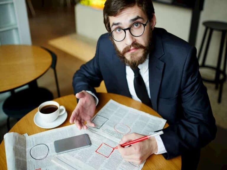Homem sentado à mesa procura emprego em jornal representando taxa de desemprego no Brasil bate recorde