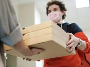 Imagem de um entregador de pizza simbolizando a ação de delivery do Santander