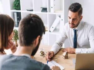 um homem apontando uma cláusula de contrato com a caneta e outras duas pessoas ouvindo as recomendações, processo de alienação fiduciária