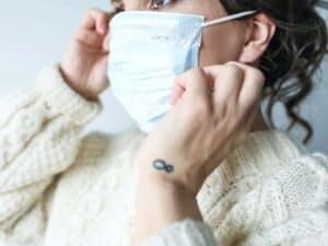 Imagem de uma mulher de máscara representando a notícia