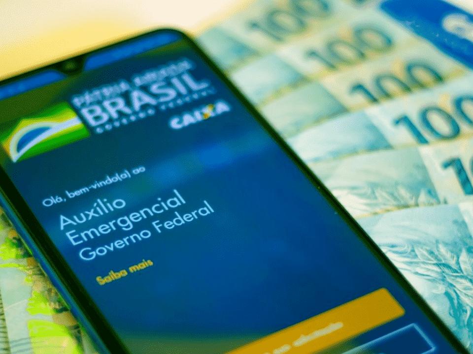 foto do aplicativo do auxílio emergencial e notas de real, representando auxílio emergencial para bolsa família