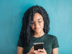 Imagem de uma jovem usando o celular, representando a notícia em que Banco Original lança pré-cadastro do Pix