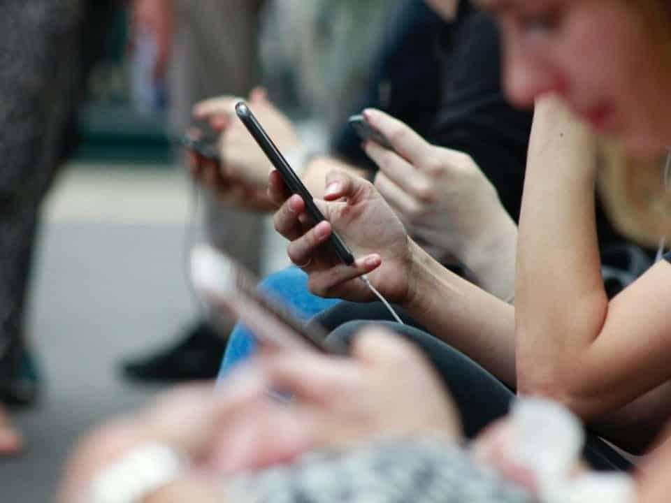 Imagem de uma pessoa usando o celular para ver a novidade entre Bradesco e Banco Next