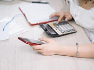 Imagem de uma pessoa usando a calculadora para entender seu salário líquido