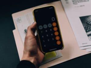 Imagem de uma pessoa usando a calculadora para saber seu décimo terceiro