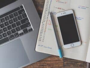 Imagem de um notebook, um celular e uma agenda em uma mesa, simbolizando o uso da calculadora de dias úteis